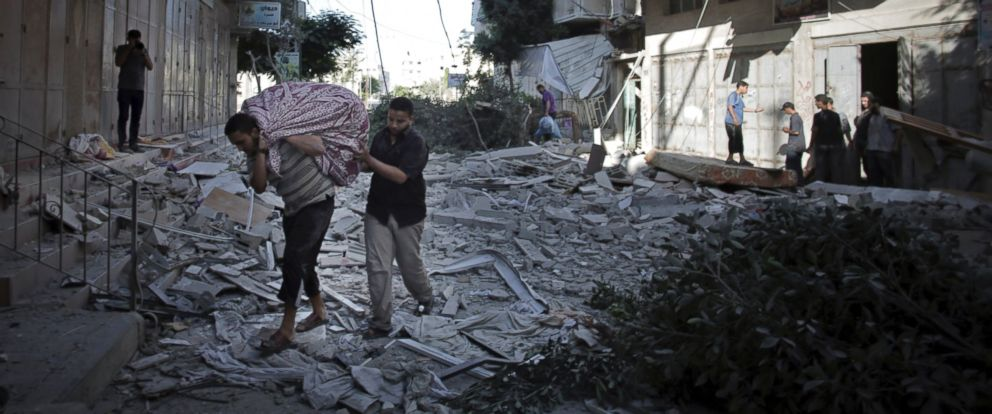 PHOTO: Palestinians salvage what they can of their belongings from the rubble of their destroyed house following an early morning Israeli missile strike in Gaza City, July 16, 2014.