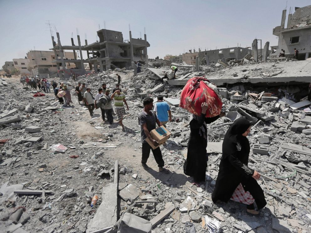 PHOTO: Palestinians carry their belongings after salvaging them from their destroyed houses in the town of Beit Hanoun, Gaza Strip, Aug. 1, 2014.