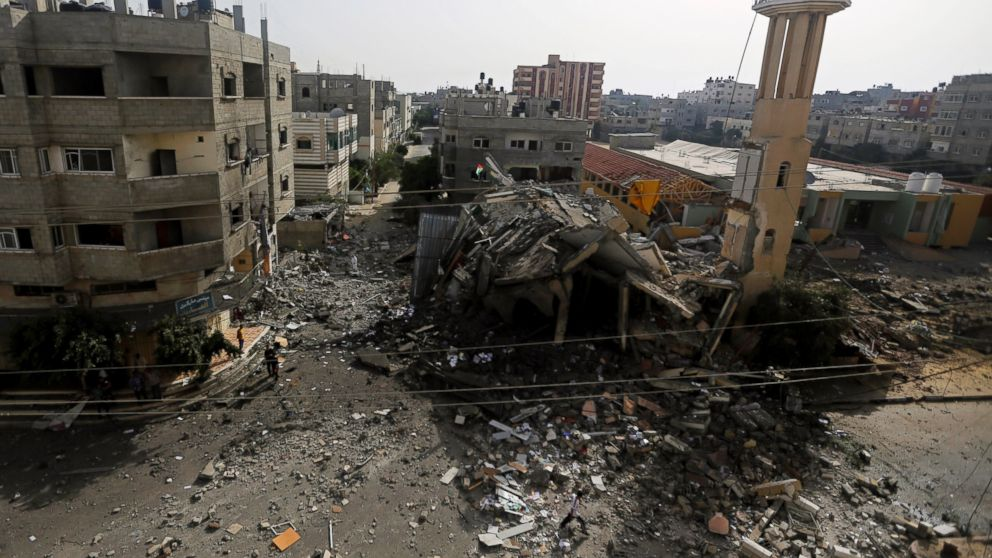 PHOTO: Palestinians walk around the ruins of the Al-Tawfeeq Mosque after it was hit by an overnight Israeli missile strike in the Nuseirat refugee camp, central Gaza Strip, Saturday, July 12, 2014.