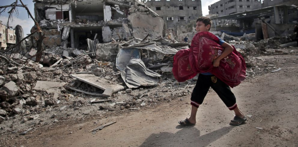 PHOTO: A Palestinian boy carries pillows as he passes by destroyed houses, during a 12-hour cease-fire in Gaza Citys Shijaiyah neighborhood, Saturday, July 26, 2014.