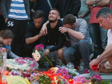 PHOTO: People mourn behind flower tributes near the Olympia shopping center where a shooting took place leaving nine people dead the day before, in Munich, July 23, 2016.