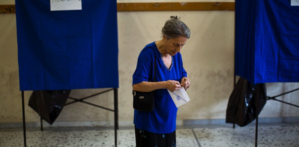 PHOTO: A woman holds her ballot paper before casting it at a polling station in Athens, Sunday, July 5, 2015.