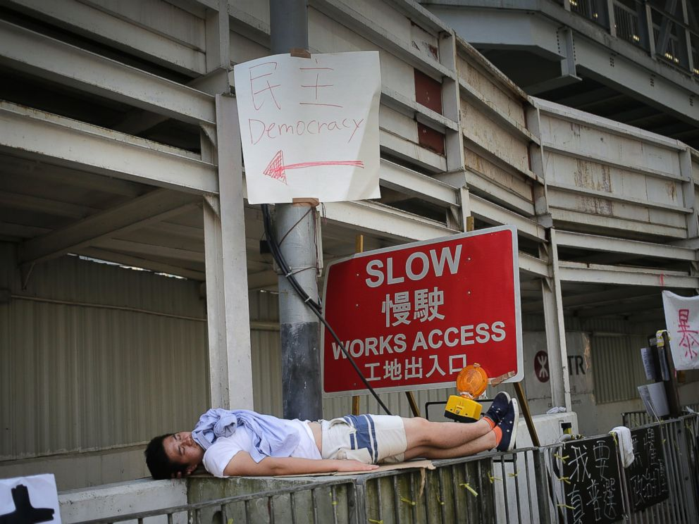 PHOTO: A pro-democracy activist sleeps on the sidewalk after an overnight protest, Sept. 30, 2014, in Hong Kong.