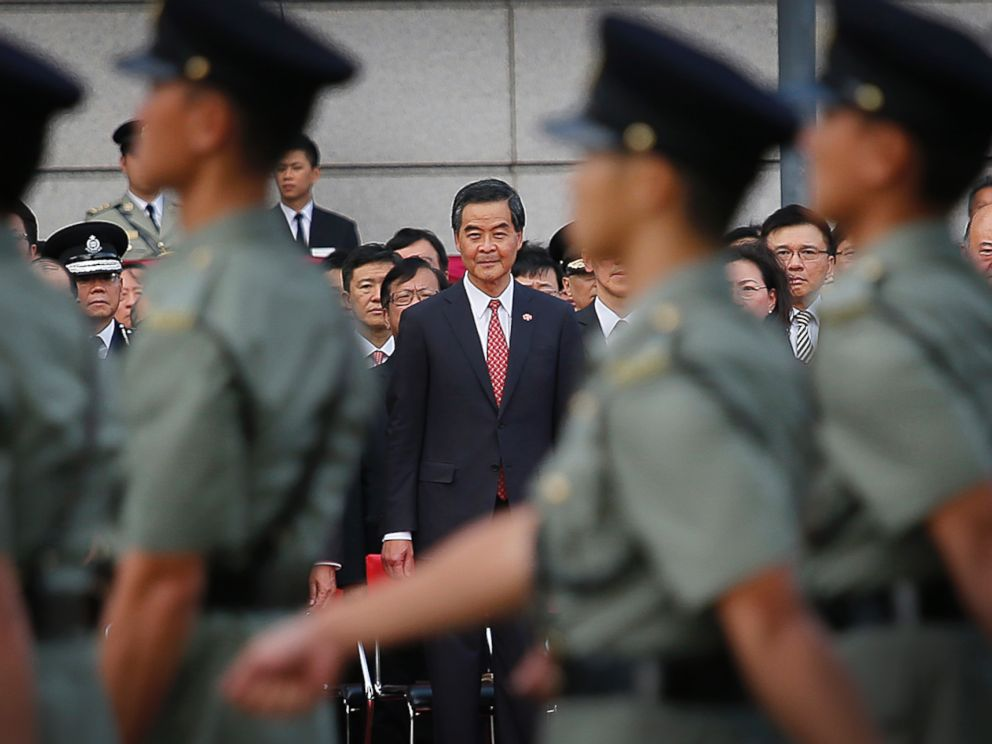 PHOTO: Hong Kongs Chief Executive Leung Chun-ying, center, watches as military personnel march during a flag-raising ceremony on Wednesday, Oct. 1, 2014 in Hong Kong.