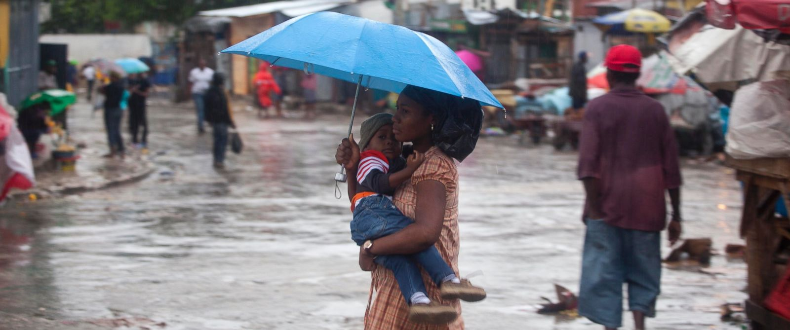 PHOTO: A woman carrying a child walks in the rain triggered by Hurricane Matthew in Port-au-Prince, Haiti, Oct. 4, 2016.
