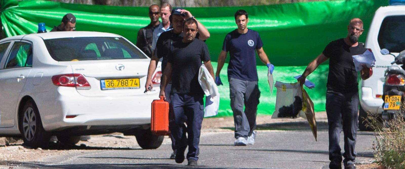 PHOTO: Israeli forensic police officers carry evidence bags from a forest in Jerusalem, July 2, 2014, after a Palestinian teen was found murdered.