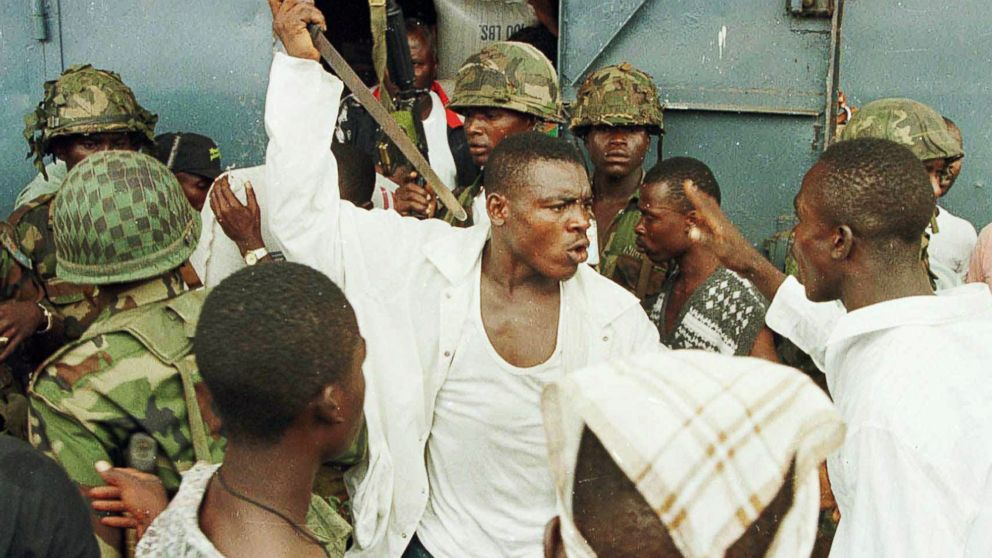 "PHOTO: Joshua Milton Blahyi, a former Liberian factional fighter known as ""General Butt Naked"", threatens a fellow combatant with a knife during an argument outside the Barclay Training Center army barracks"