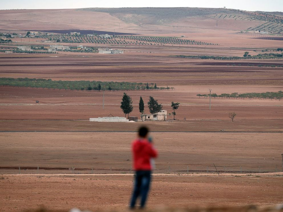 A boy uses a mobile phone to photograph the western outskirts of Kobani, Syria on the distance, as he stands on a hilltop on the outskirts of Suruc, at the Turkey-Syria border, Oct. 19, 2014.