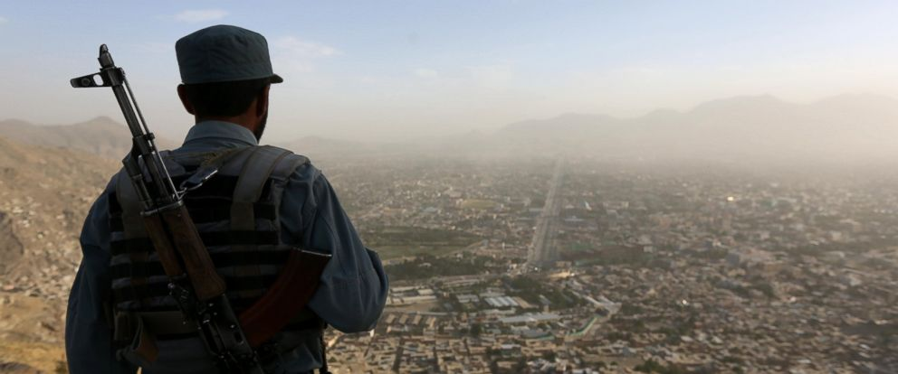 PHOTO: An Afghan policeman looks over the city of Kabul on June 21, 2016.