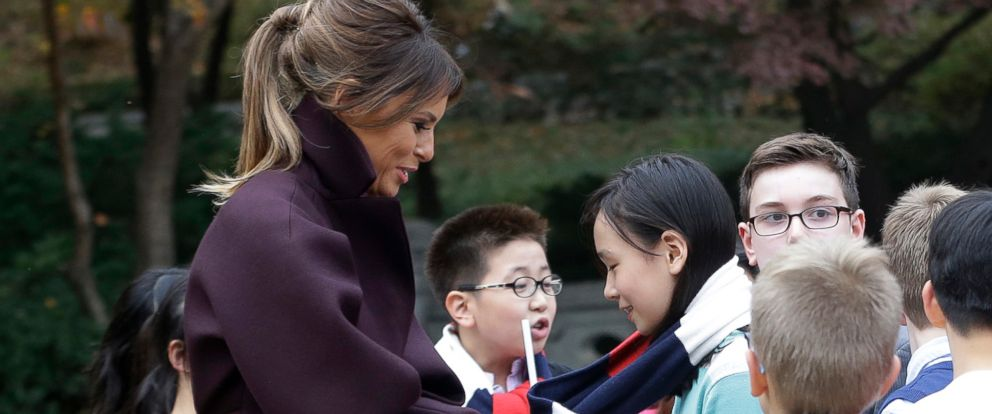 U.S. first lady Melania Trump puts on a scarf to a South Korean girl at the presidential Blue House in Seoul, South Korea, Tuesday, Nov. 7, 2017.