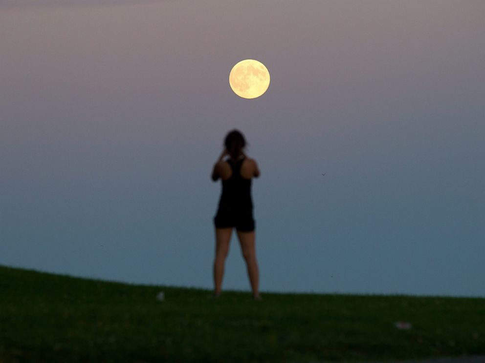 PHOTO: Queens University student Lindsay Meier takes a picture of the moon as it rises over Lake Ontario in Kingston, Ontario, Sept. 8, 2014.