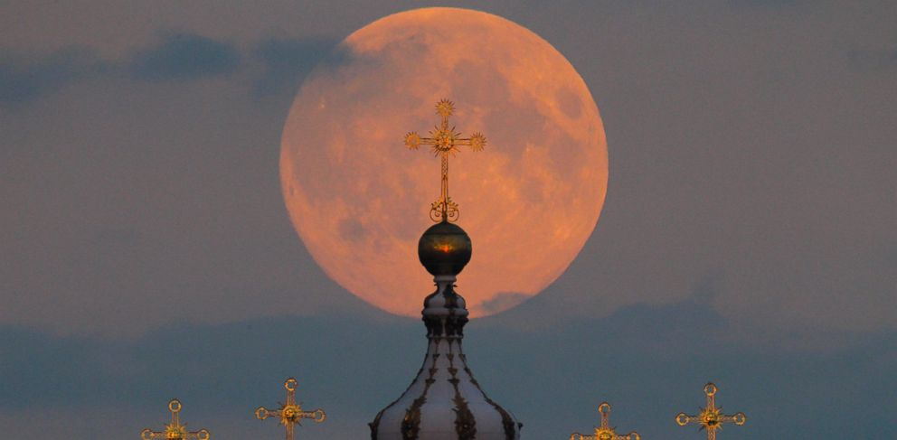 PHOTO: The full moon is seen rising in the sky above the domes of the Smolny Cathedral in St. Petersburg, Russia, Sept. 8, 2014.