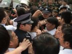 PHOTO: Relatives of Chinese passengers onboard the Malaysia Airlines plane MH370 scuffle with Chinese police officers outside the Malaysian embassy in Beijing, China, March 25, 2014.