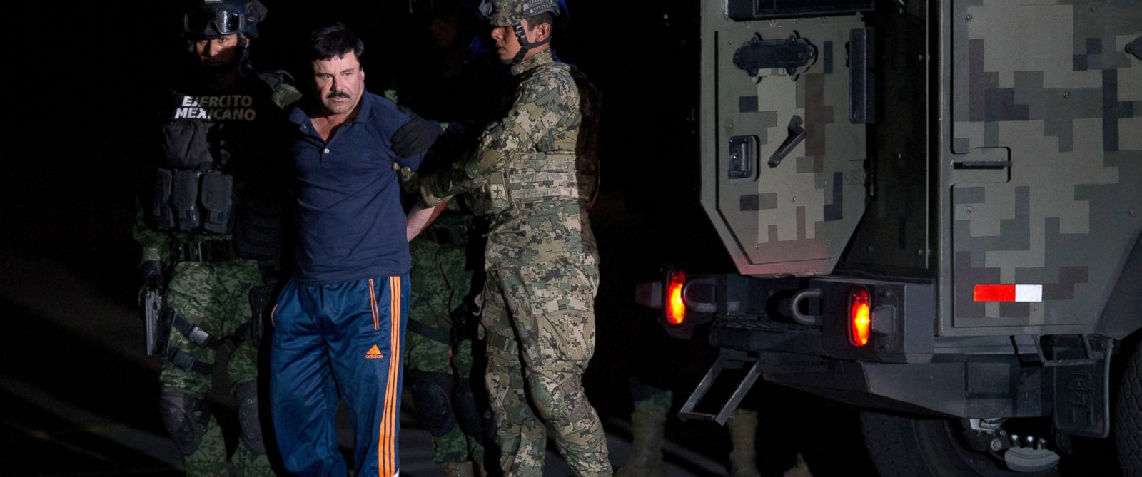 "PHOTO: Mexican drug lord Joaquin ""El Chapo"" Guzman is escorted by soldiers and marines to a waiting helicopter, at a federal hangar in Mexico City, Friday, Jan. 8, 2016."