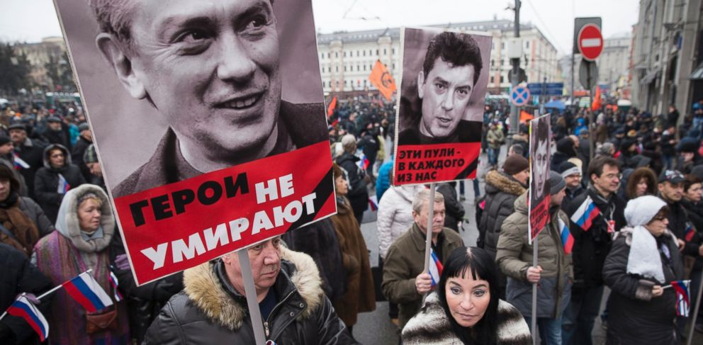 People carry portraits of opposition leader Boris Nemtsov who was gunned down on Friday, Feb. 27, 2015 near the Kremlin, with words reading those bullets for everyone of us, heros never die! in Moscow, Russia, Sunday, March 1, 2015.