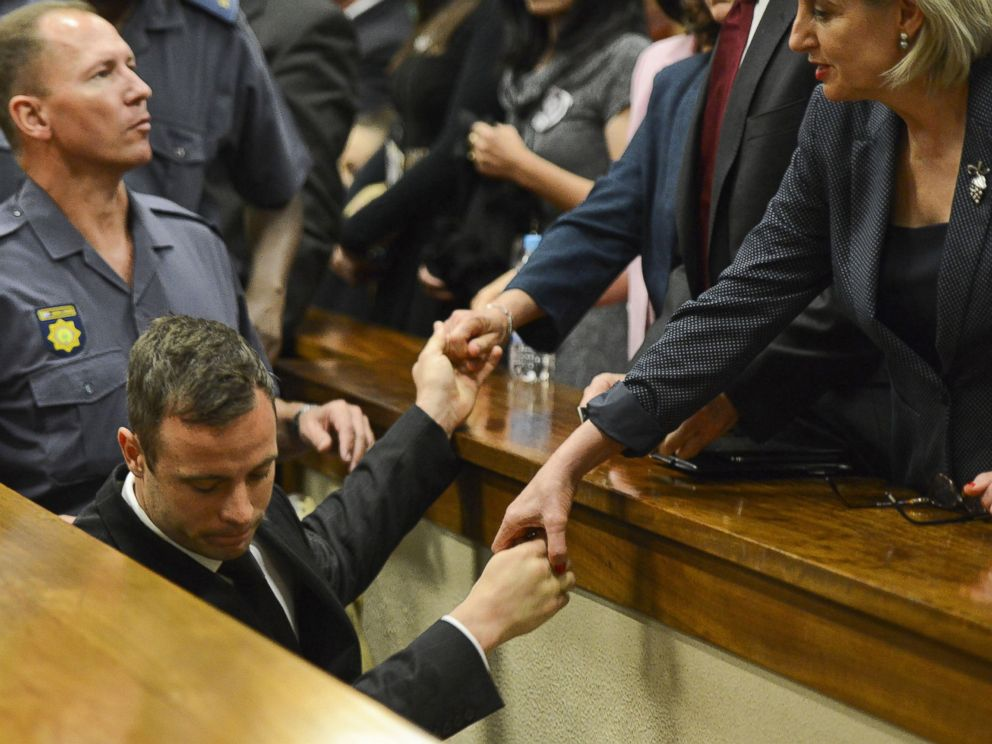 PHOTO: Oscar Pistorius, center, touches hands with family members as he is led down to the cells of the court in Pretoria, South Africa, Oct. 21, 2014.