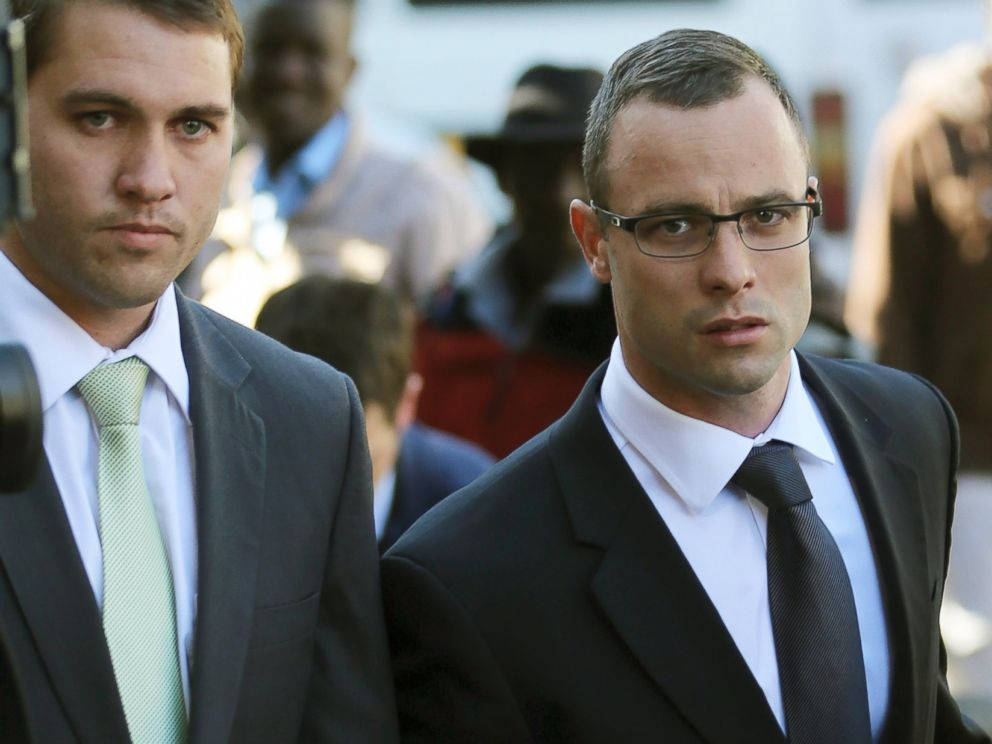 PHOTO: Oscar Pistorius, right, walks outside the high court in Pretoria, South Africa, May 14, 2014.