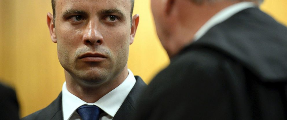 PHOTO: Oscar Pistorius talks to to his defense attorney Barry Roux before the proceedings get under way at the high court in Pretoria, South Africa, March 24, 2014.