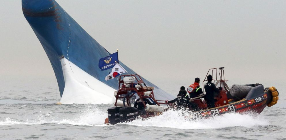 PHOTO: South Korean coast guard officers try to rescue passengers from a ferry sinking in the water off the southern coast near Jindo, south of Seoul, South Korea, April 16, 2014.injured.