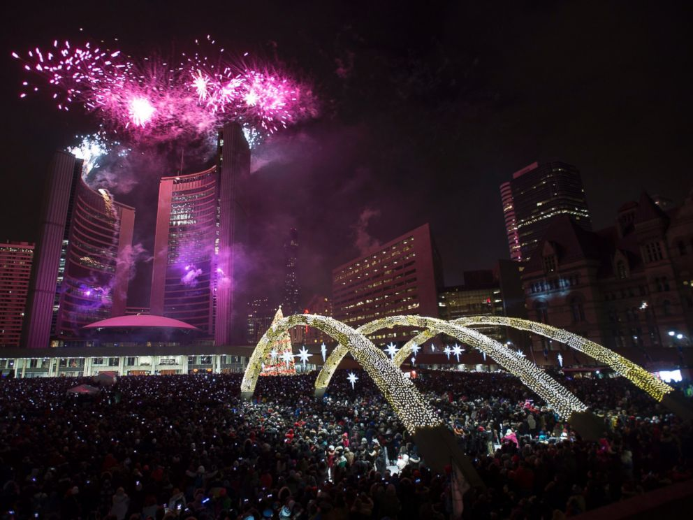 Fireworks explode in front of City Hall as revelers pack Nathan Phillips Square for New Years celebrations in Toronto on Thursday, Jan. 1, 2015.