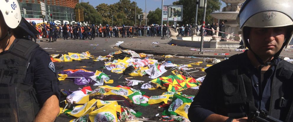 Bodies of victims are covered with flags and banners as police officers secure the area after an explosion in Ankara, Turkey, Saturday, Oct. 10, 2015.