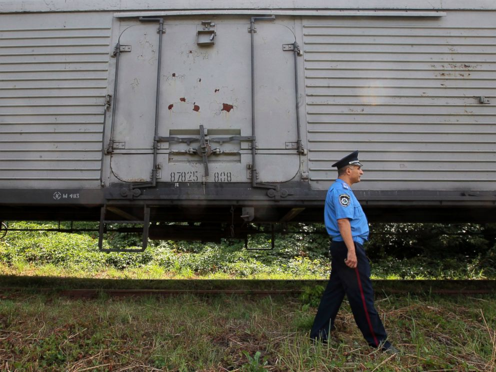 PHOTO: A police officer walks past a refrigerated train loaded with bodies of the passengers of Malaysian Airlines flight MH17 at Kharkiv railway station, Ukraine, July 22, 2014.