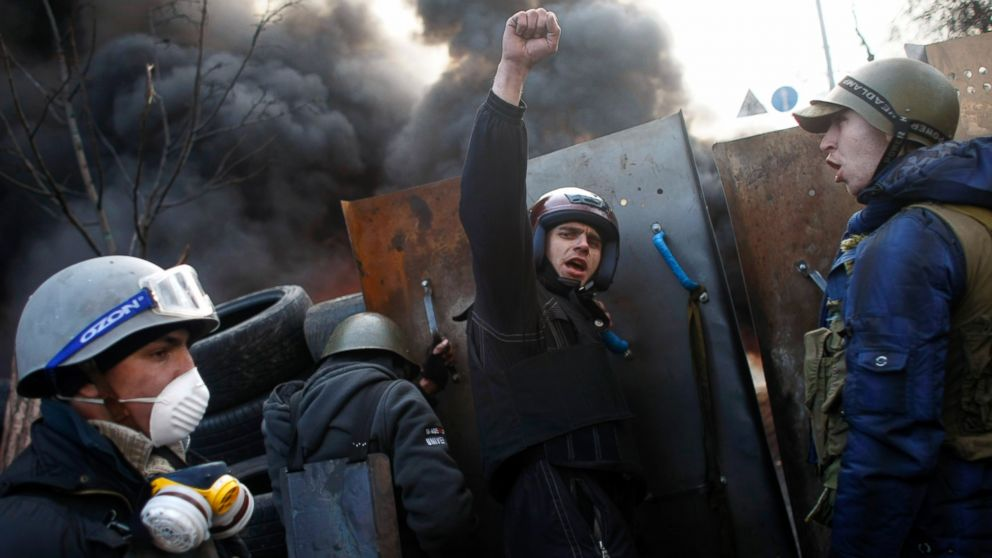 "PHOTO: Anti-government protesters shout ""Glory to the Ukraine"" as they man a barricade at Independence Square in Kiev, Ukraine, Feb. 21, 2014."