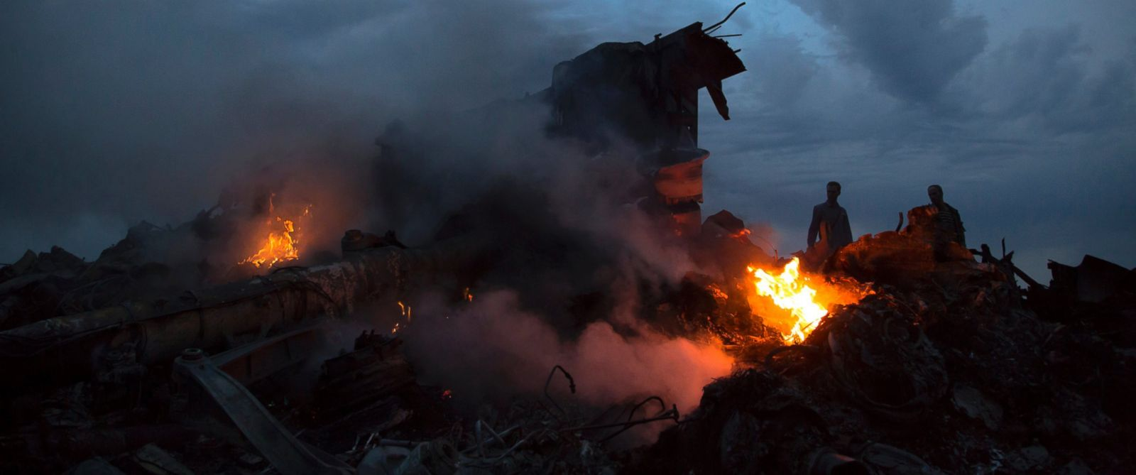 PHOTO: People walk amongst the debris at the crash site of a passenger plane near the village of Hrabove, Ukraine, Thursday, July 17, 2014. Ukraine said a passenger plane was shot down Thursday as it flew over the country.