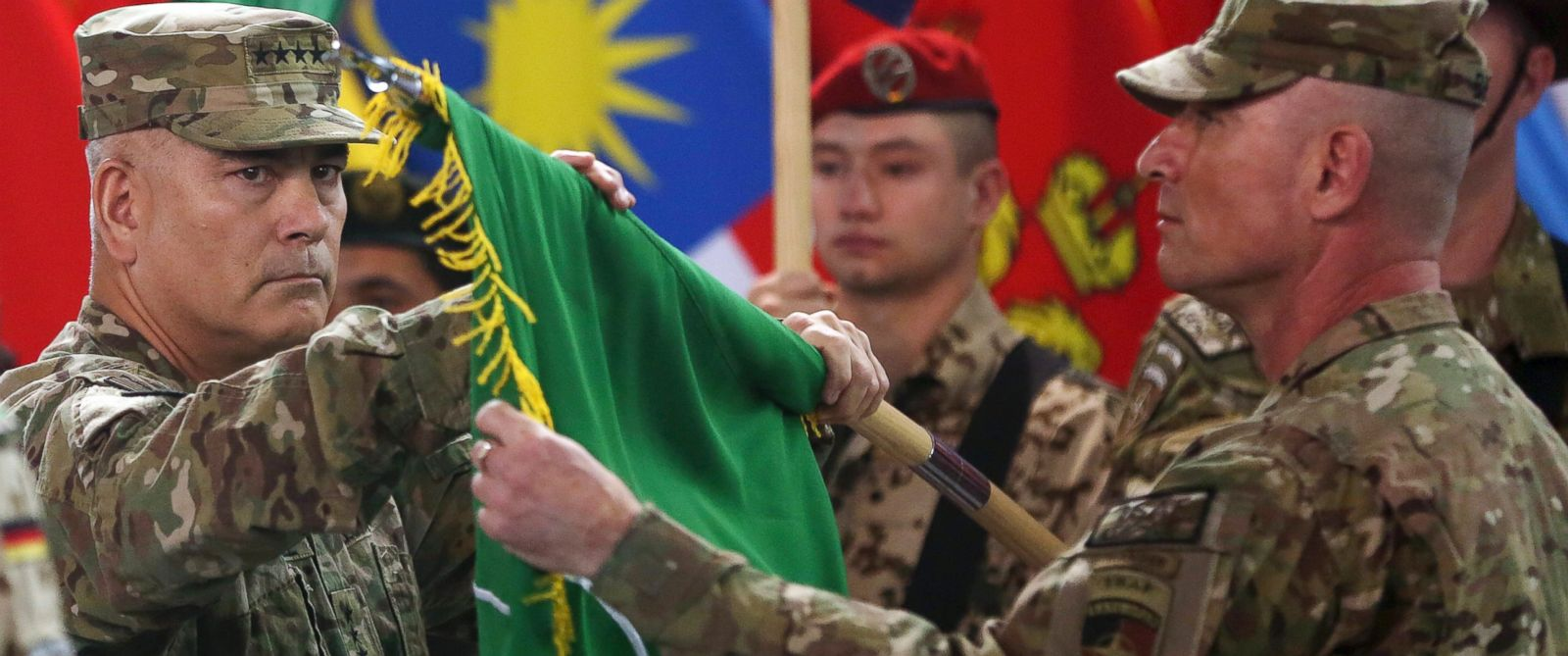 "PHOTO: Commander of the International Security Assistance Force (ISAF), Gen. John Campbell, left, and Command Sgt. Maj. Delbert Byers open the ""Resolute Support"" flag during a ceremony at the ISAF headquarters in Kabul, Afghanistan, Dec. 28, 2014."