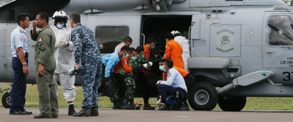PHOTO: U.S. Navy personnel from USS Sampson and National Search and Rescue Agency personnel unload the body of a victim aboard AirAsia Flight 8501 from a U.S. Navy helicopter upon arrival at the airport in Pangkalan Bun, Indonesia, Friday, Jan. 2, 2015.