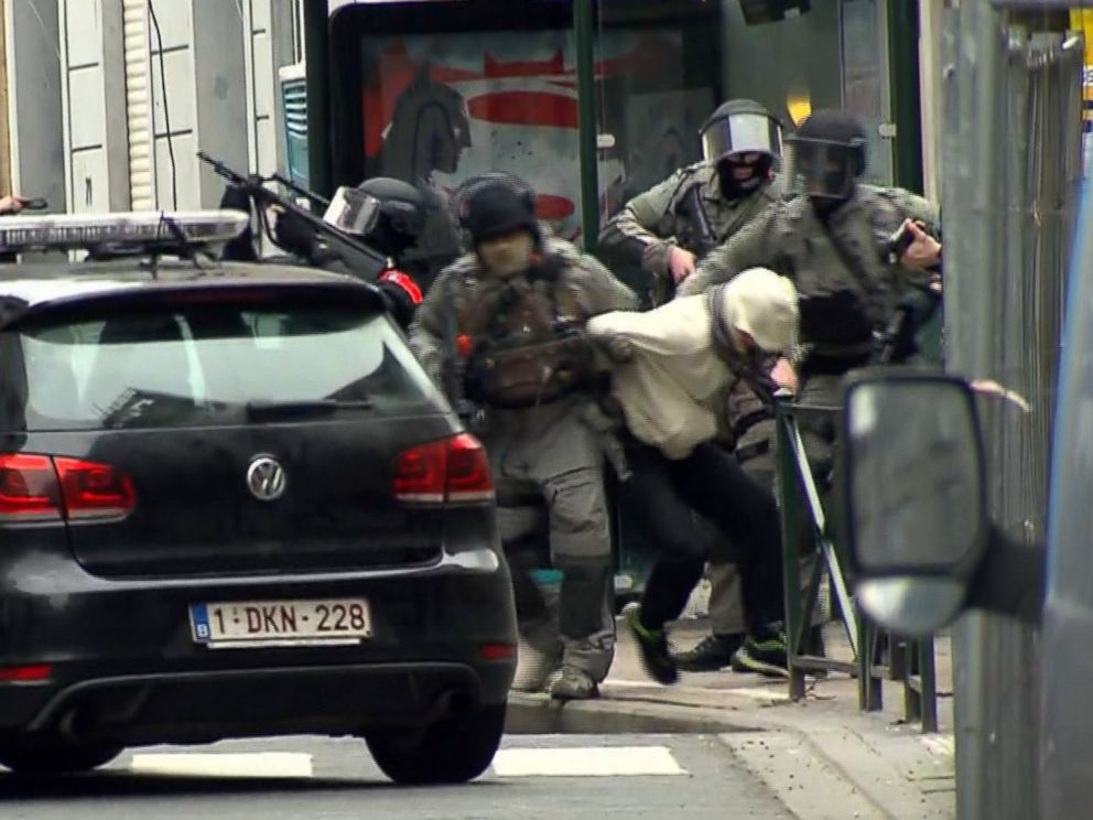 PHOTO: In this framegrab taken from VTM, armed police officers escort a suspect to a police vehicle during a raid in the Molenbeek neighborhood of Brussels,March 18, 2016.