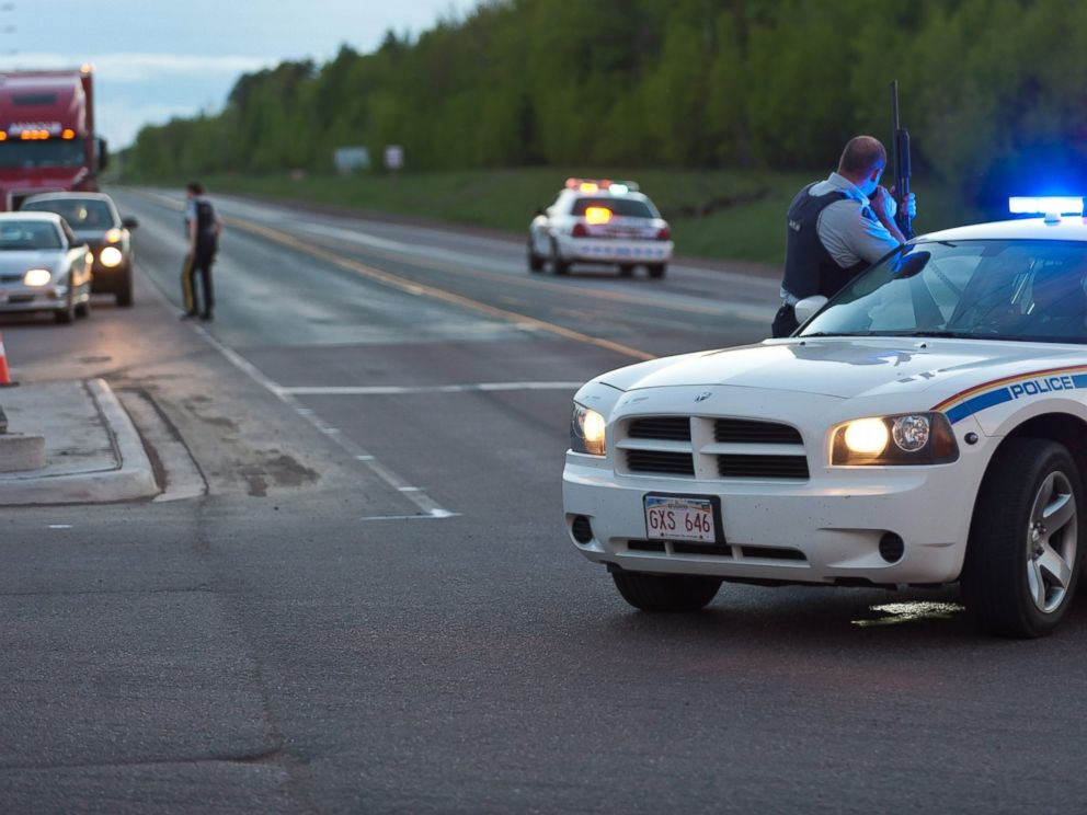 PHOTO: Royal Canadian Mounted Police officers use their vehicles to create a keep a perimeter in Moncton, New Brunswick, June 4, 2014, following a shooting.