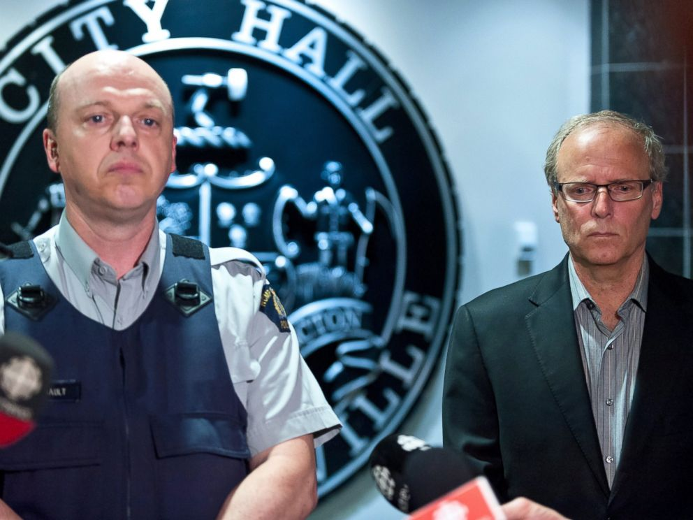 PHOTO: Royal Canadian Mounted Police officer Damien Theriault and Mayor George LeBlanc pause to collect themselves before addressing the media during a late night news conference at City Hall in Moncton, New Brunswick, June 4, 2014.