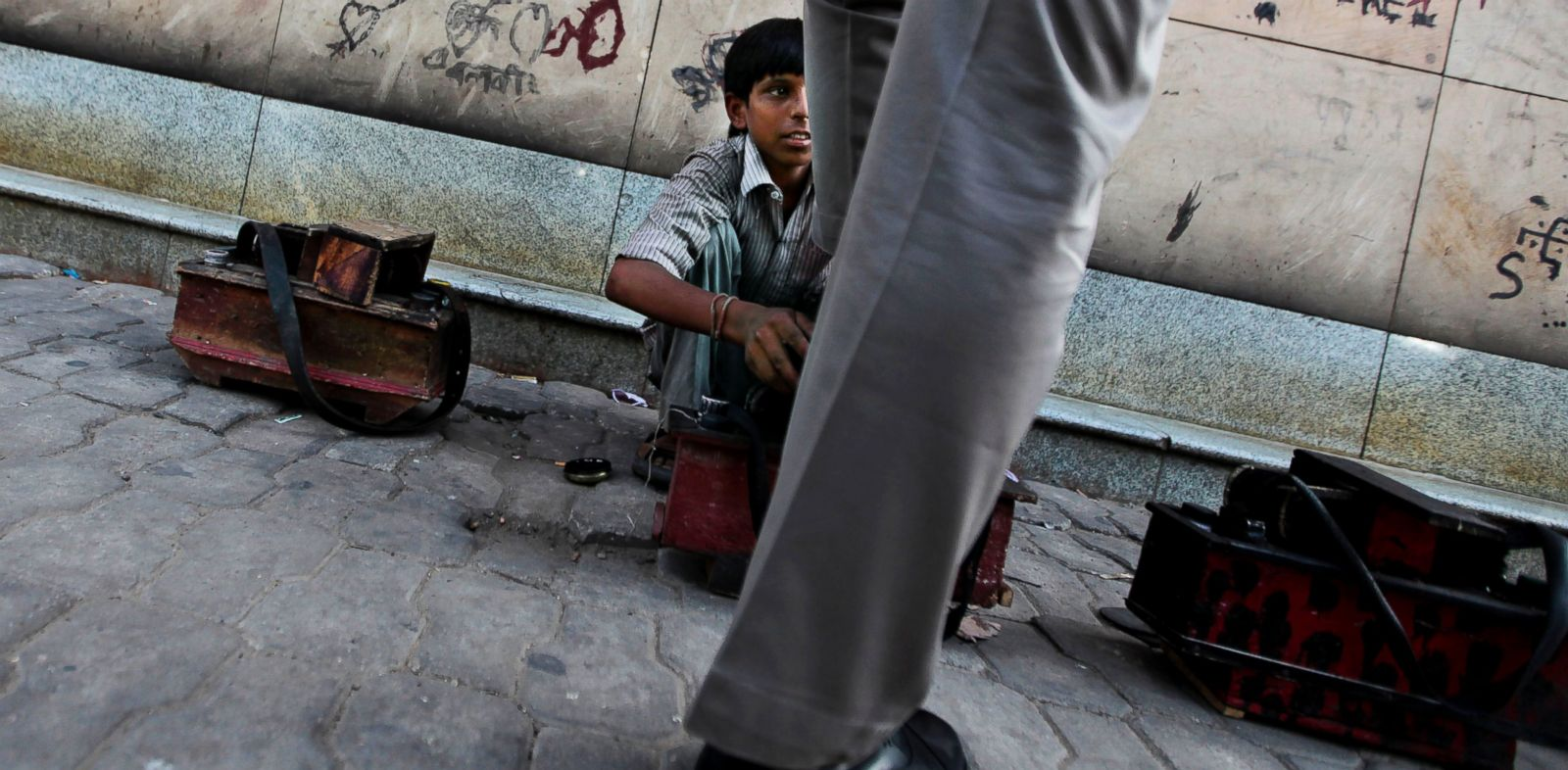 PHOTO: A young Indian boy polishes a shoe on a pavement on World Day Against Child Labor in New Delhi, India, June 12, 2012.