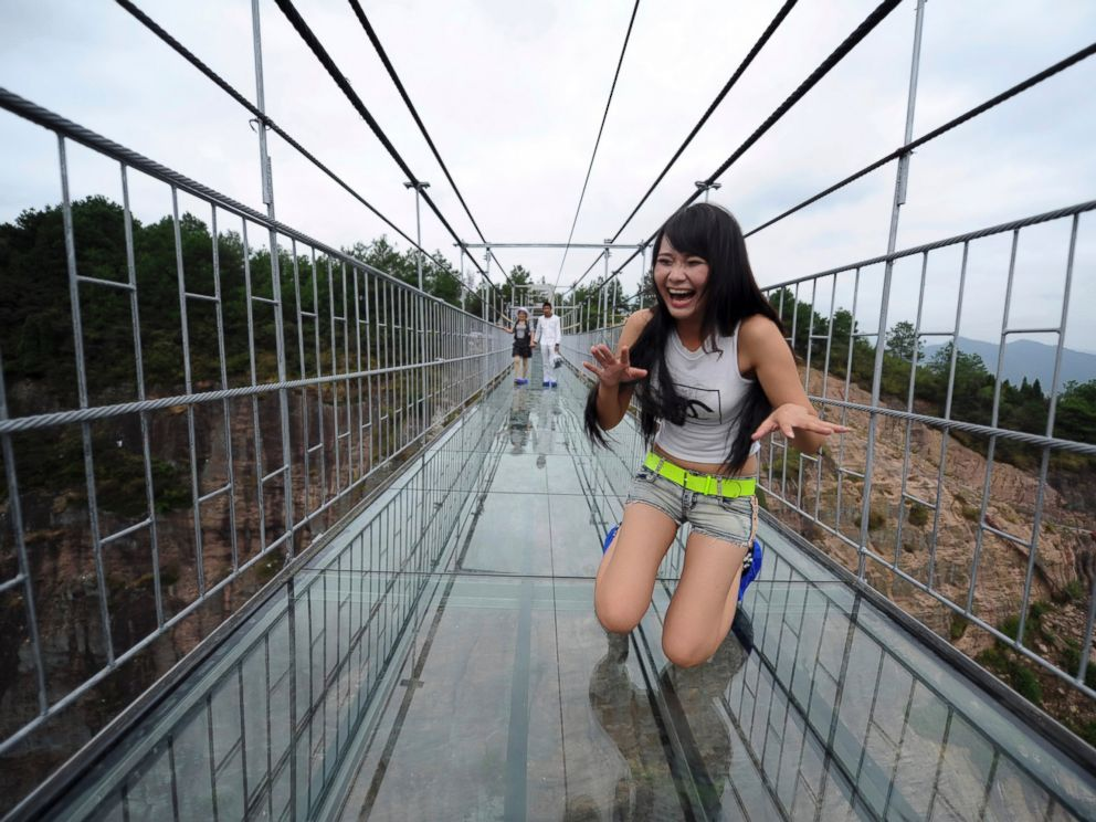 PHOTO: A woman plays around as she walks across a glass-bottomed suspension bridge in a scenic zone in Pingjiang county in southern Chinas Hunan province, Sept. 24, 2015.