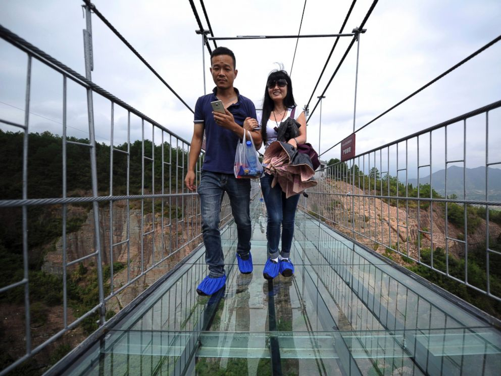 PHOTO: Visitors wear protective shoe coverings as they walk across a glass-bottomed suspension bridge in a scenic zone in Pingjiang county in southern Chinas Hunan province, Sept. 24, 2015.