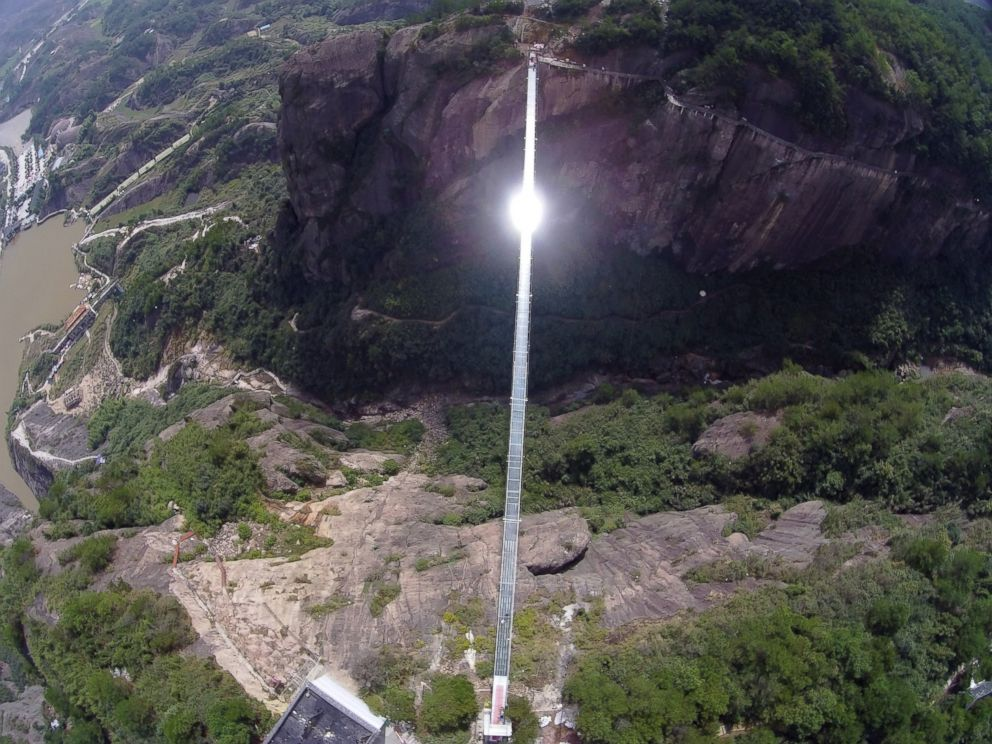 PHOTO: Sunlight reflects off a glass-bottomed suspension bridge as seen from the air in a scenic zone in Pingjiang county in southern Chinas Hunan province, Sept. 24, 2015.