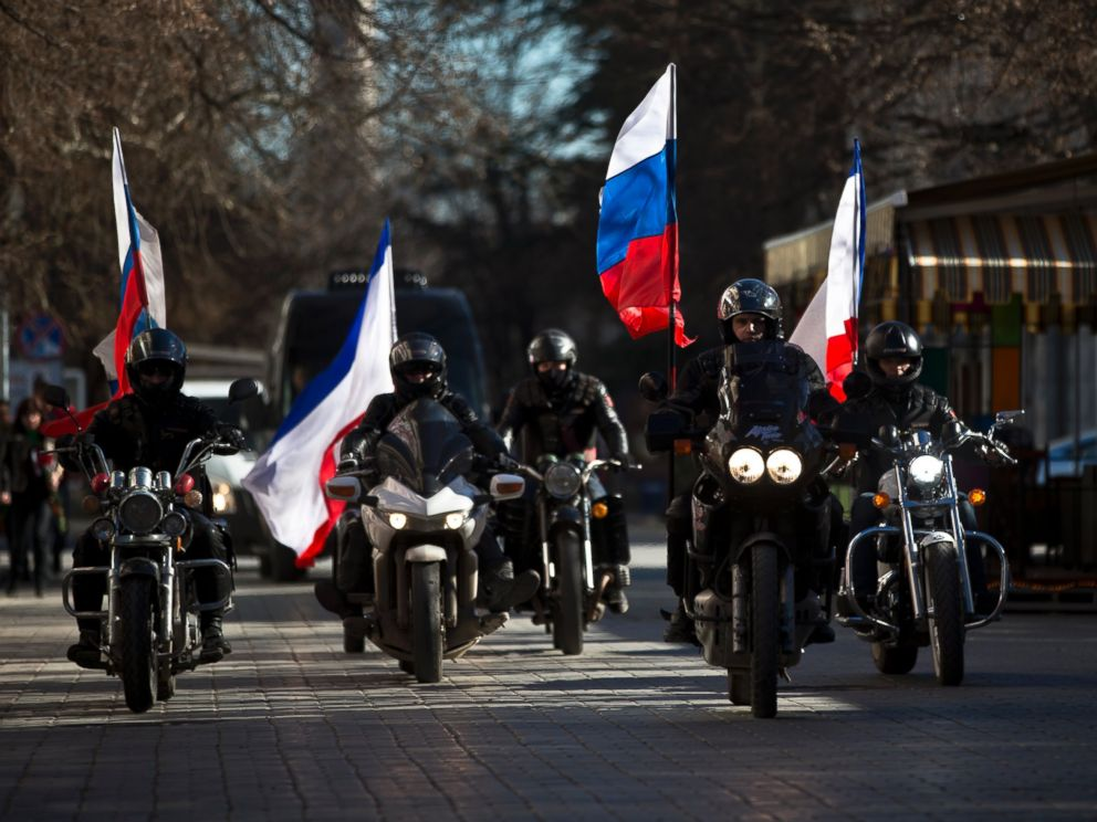 PHOTO: People on motorcycles decorated with Russian and Crimean flags drive in front of a van transporting the coffins of Ukrainian soldiers during their funeral in Simferopol, Crimea, Saturday, March 22, 2014.