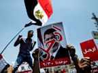 PHOTO: Opponents of Egypts Islamist President Mohammed Morsi hold posters with Arabic that reads, Leave, as they protest outside the presidential palace in Cairo, Egypt, Sunday, June 30, 2013.
