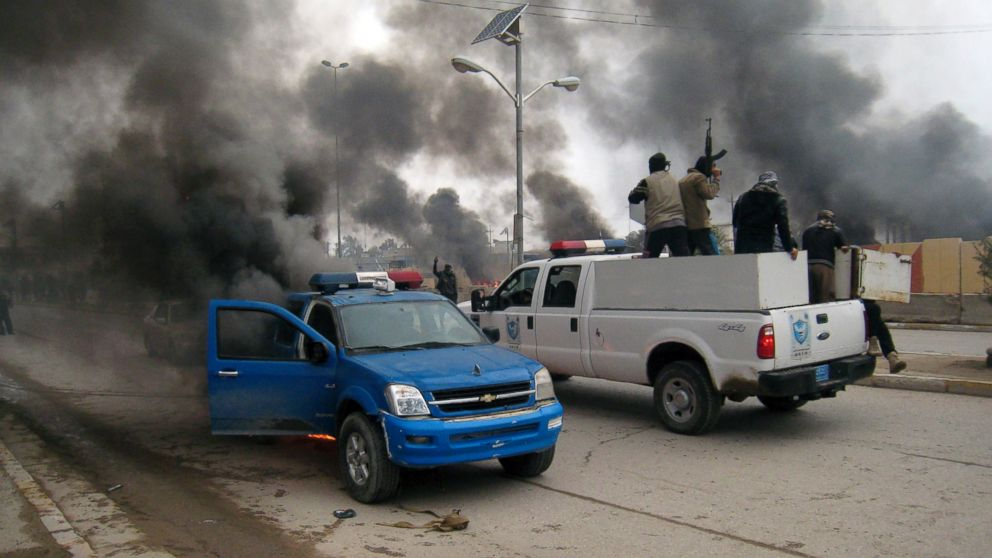 PHOTO: Al-Qaida fighters patrol in a commandeered police truck passing burning police vehicles in front of the main provincial government building, in Fallujah, 40 miles (65 kilometers) west of Baghdad, Iraq, Jan. 1, 2014.