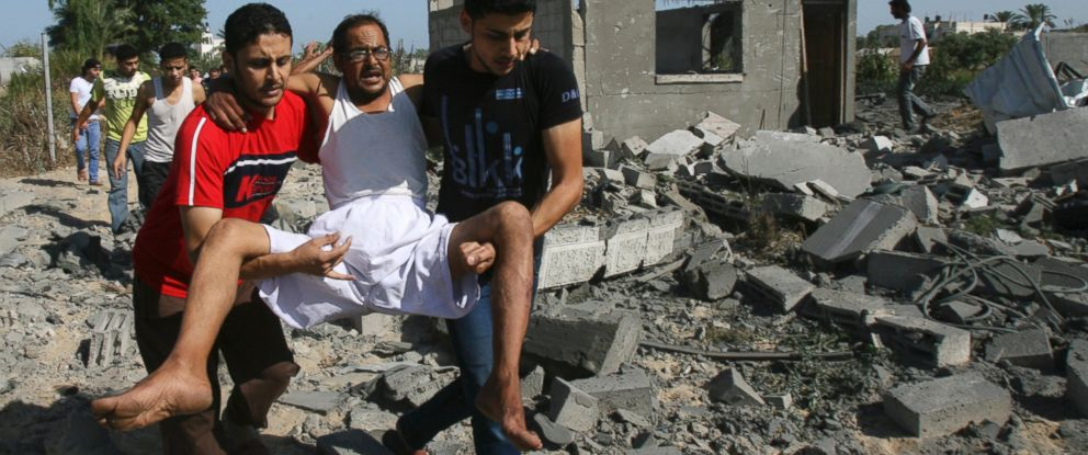 PHOTO: Palestinians help a man wounded as they walk over the rubble of destroyed buildings
