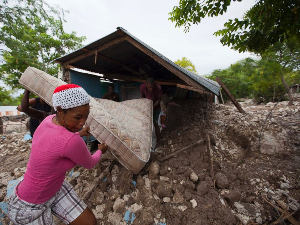 PHOTO: Residents salvage a mattress from a home partially submerged in mud from a mudslide triggered by Tropical Storm Erika, Aug. 29, 2015, in Montrouis, Haiti.