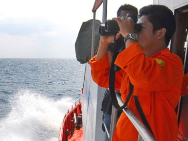 PHOTO: A member of the Indonesian National Search and Rescue Agency uses binoculars to scan the horizon during a search operation for the missing Malaysia Airlines Boeing 777 on the waters of the Strait of Malacca on March 12, 2014.