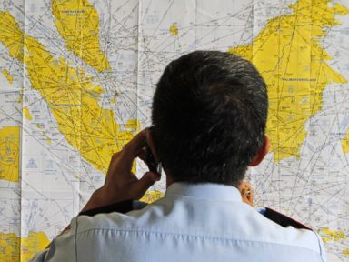 PHOTO: An airport official checks a map of Indonesia at the crisis center set up by local authority for the missing AirAsia flight QZ8501, at Juanda International Airport in Surabaya, East Java, Indonesia, Dec. 28, 2014.