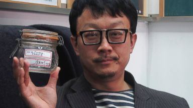 PHOTO: Beijing artist Liang Kegang poses with the jar of fresh air collected in Provence, France, in an art gallery in Beijing.