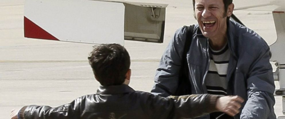 PHOTO: Spanish reporter Javier Espinosa, reacts as his son Yerai runs towards him upon his arrival at the military airport of Torrejon in Madrid, Sunday, March 30, 2014.