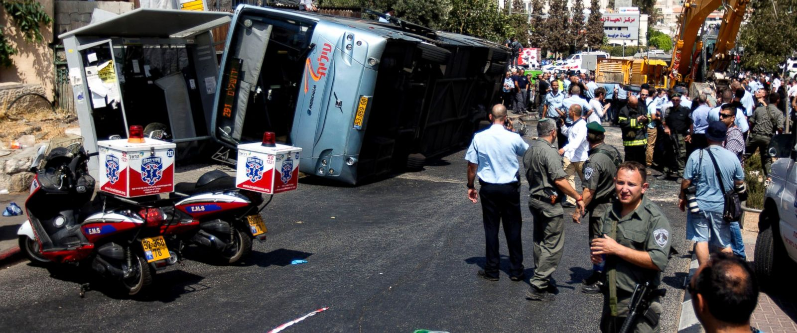 PHOTO: Israelis stand near a flipped bus at the scene of an attack in Jerusalem, Aug. 4, 2014.