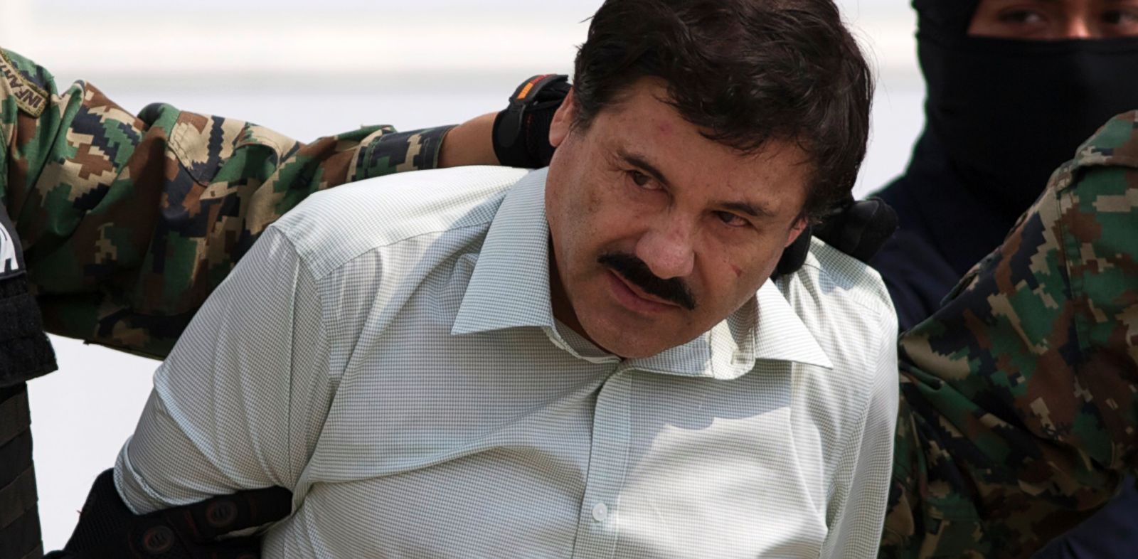 "PHOTO: Joaquin ""El Chapo"" Guzman is escorted to a helicopter in handcuffs by Mexican navy marines at a navy hanger in Mexico City, Saturday, Feb. 22, 2014."