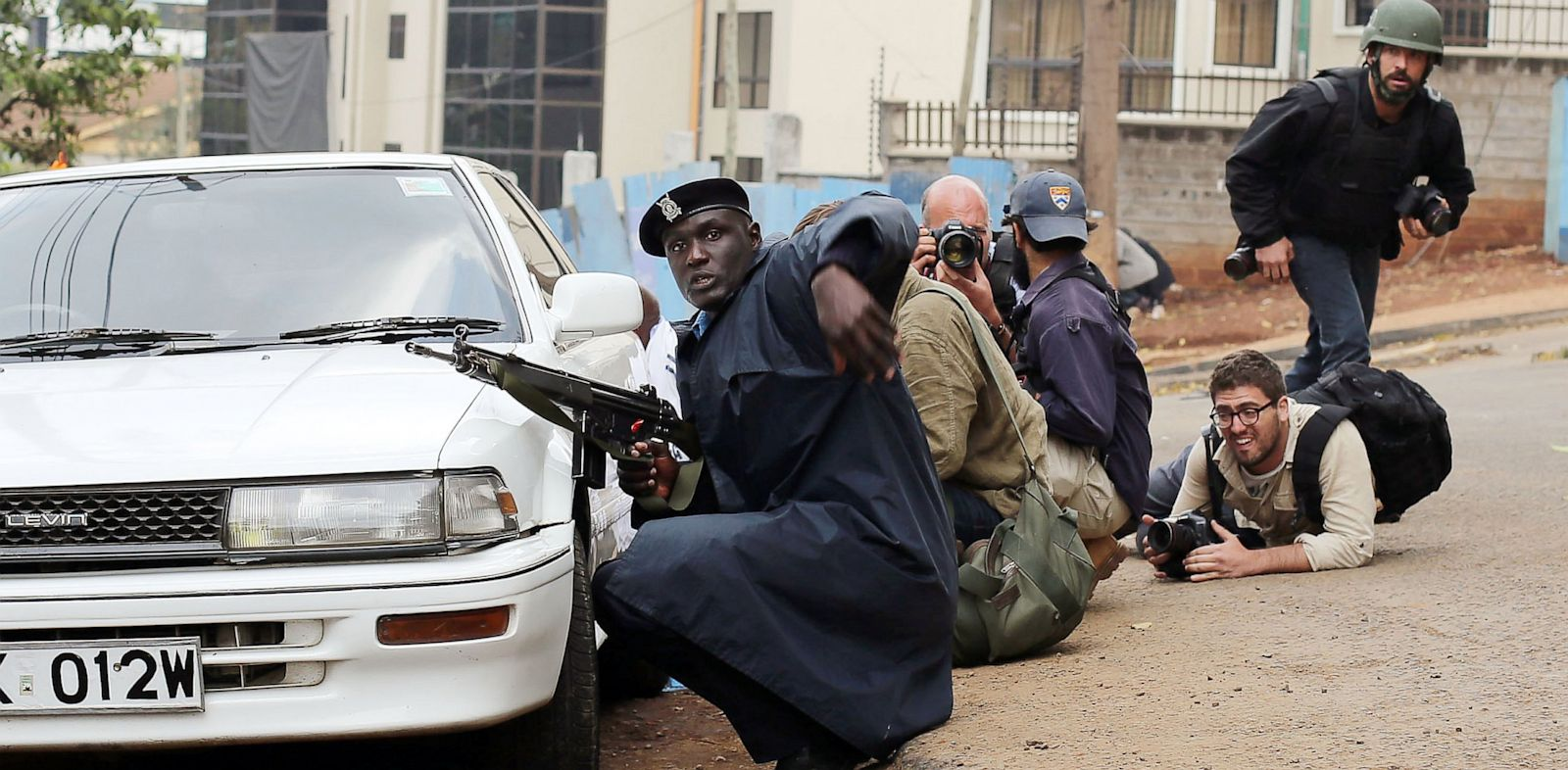 PHOTO: Kenyan security personnel and journalists duck behind a vehicle as heavy gunfire erupts from the Westgate Mall in Nairobi Kenya, Sept. 23 2013.