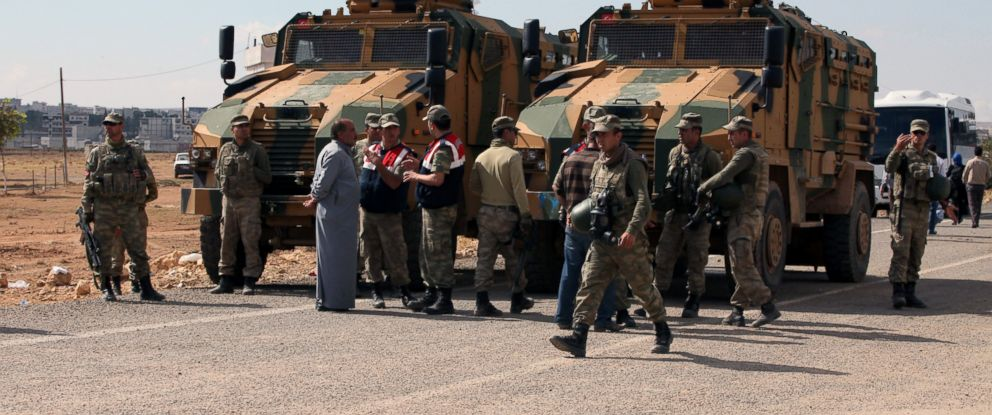 PHOTO: Turkish soldiers standby as Turkish Kurds gather nearby to express their solidarity with Kurdish fighters in Kobani, Syria, at the Turkey-Syria border near Suruc, Turkey, Sept. 29, 2014.